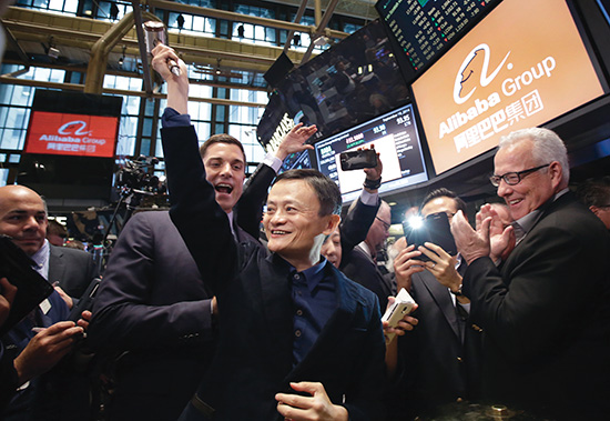 Jack Ma, center, founder of Alibaba, raises a ceremonial mallet before striking a bell during the company's IPO at the New York Stock Exchange, Friday, Sept. 19, 2014 in New York. The stock is to start trading Friday under the ticker